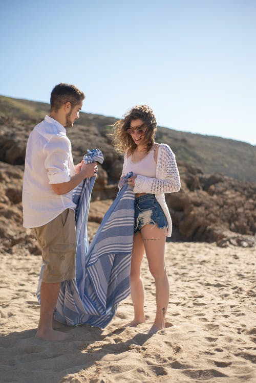Couple Standing on Sand with Blue and white Striped Linen