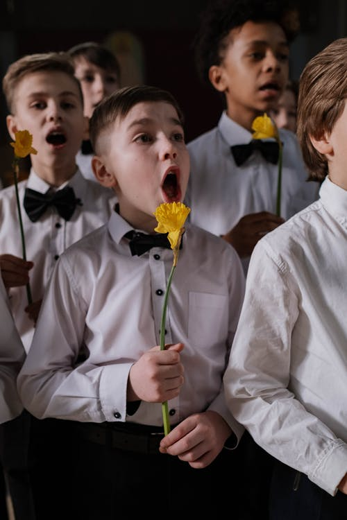 Boy in White Dress Shirt Holding Yellow Flower