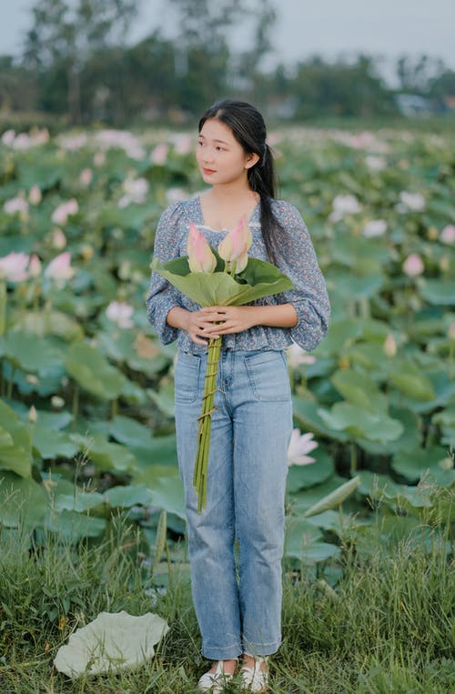Woman in Blue Denim Jeans Standing on Green Grass