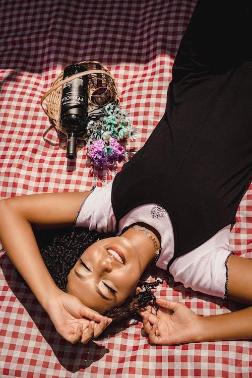 Woman in Black Sleeveless Dress Lying on Bed