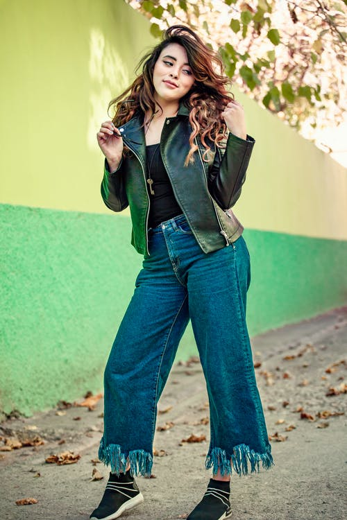 A Woman Wearing a Leather Jacket and Denim Pants