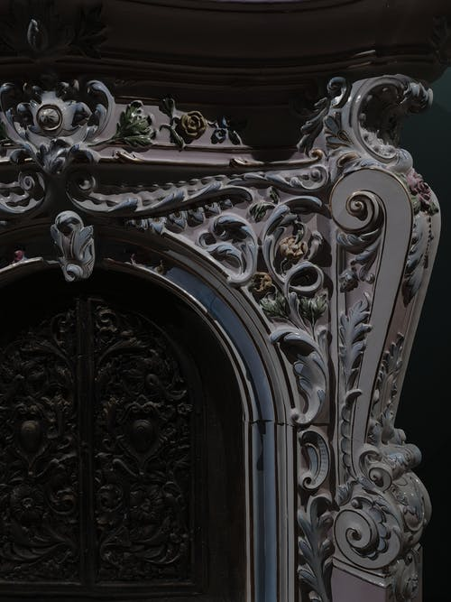 Floral and leaf shaped carved relief on front part of aged classic fireplace in house