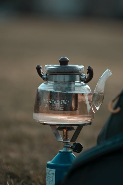 Glass teapot with water heating on gas burner at campsite during hike in nature