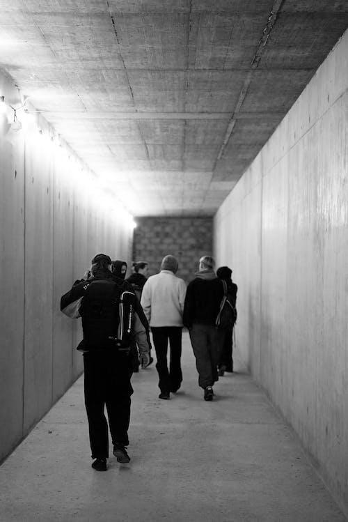 Grayscale Photo of People Walking on a Hallway