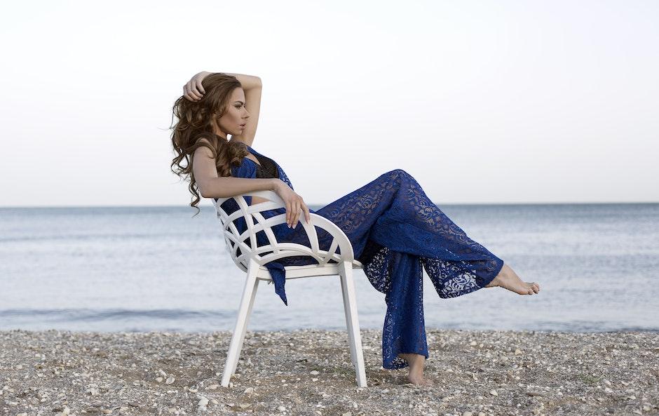Woman Wearing Blue Two-piece Dress Sitting on White Armchair Near Beach