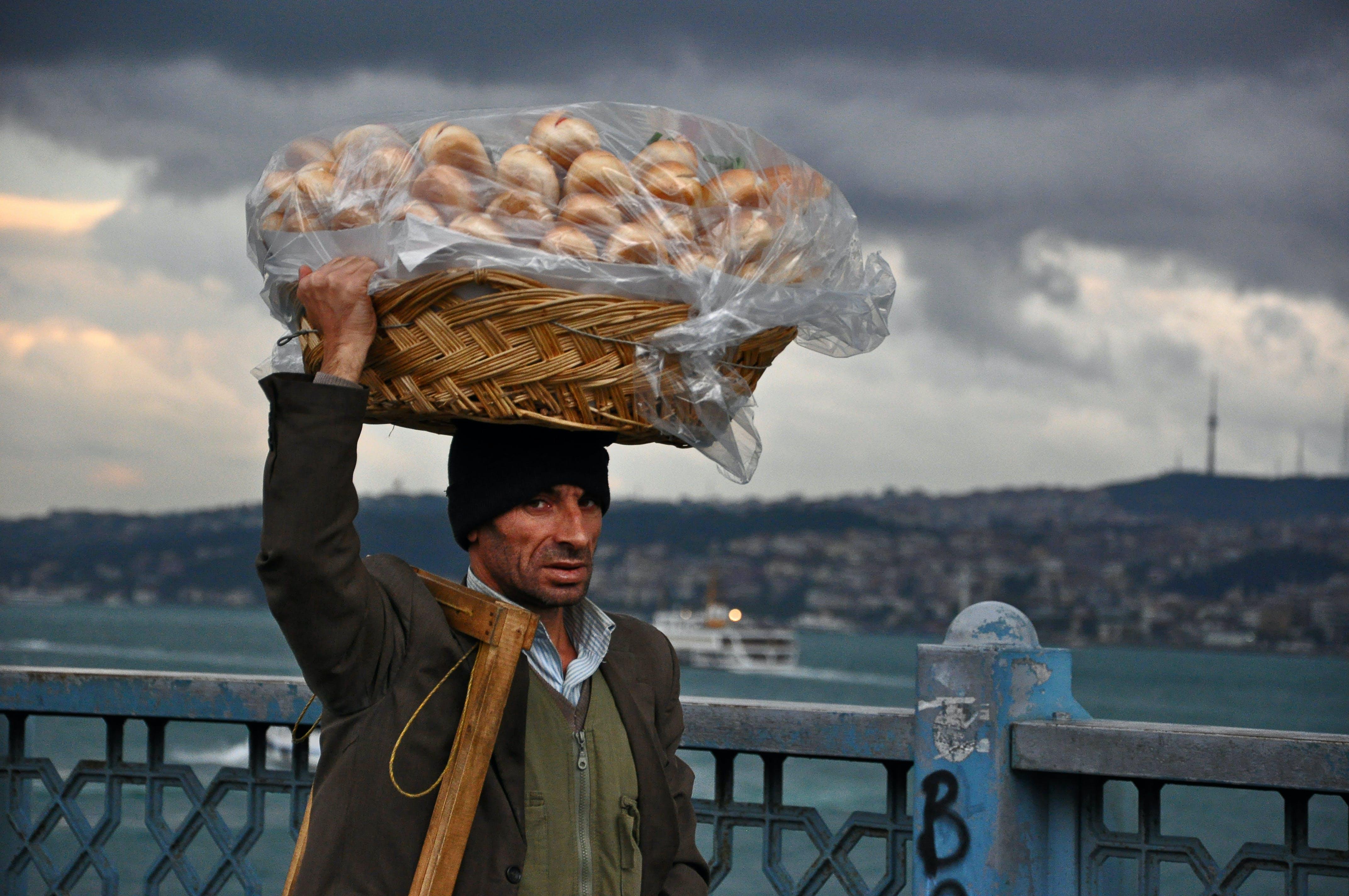 Basket on Man's Head Under Cloudy Sky