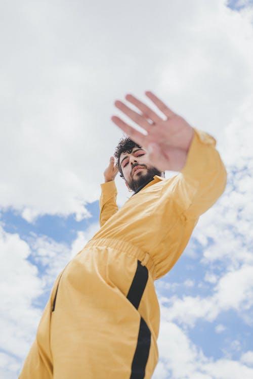 Man in Yellow Long Sleeve Shirt Raising His Right Hand