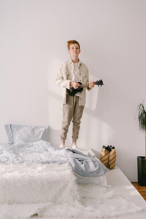 白色禮服襯衫和米色褲子拿著黑色的數碼單反相機的男人