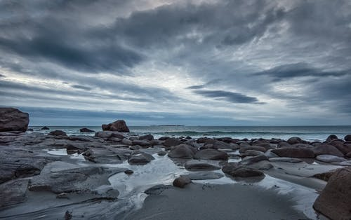 Rocky Shore Under Blue Sky and White Clouds