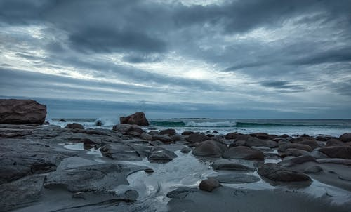 Gray and Black Rocks on Seashore Under Blue and White Cloudy Sky