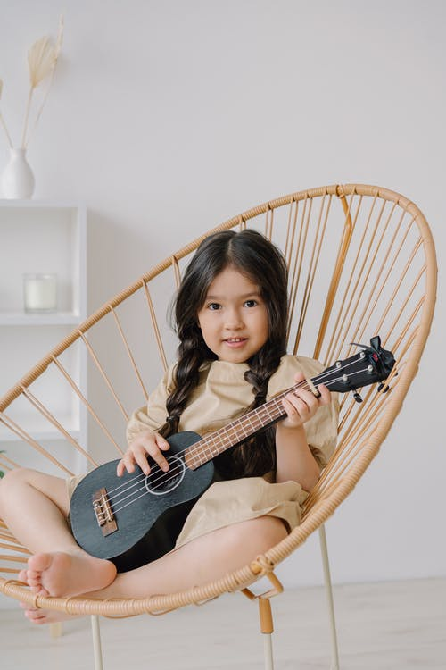 Pretty Girl Sitting On Rattan Chair With A Ukelele