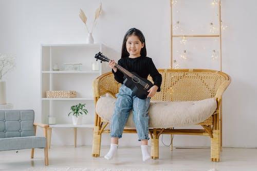 Girl in Black Shirt Holding Black Ukulele Sitting on Brown Wicker Chair