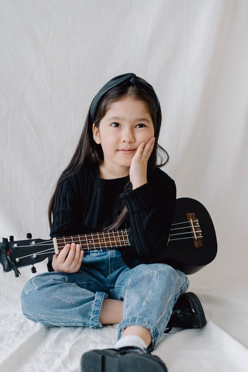 Photo of a Cute Kid in Denim Jeans Holding a Ukulele