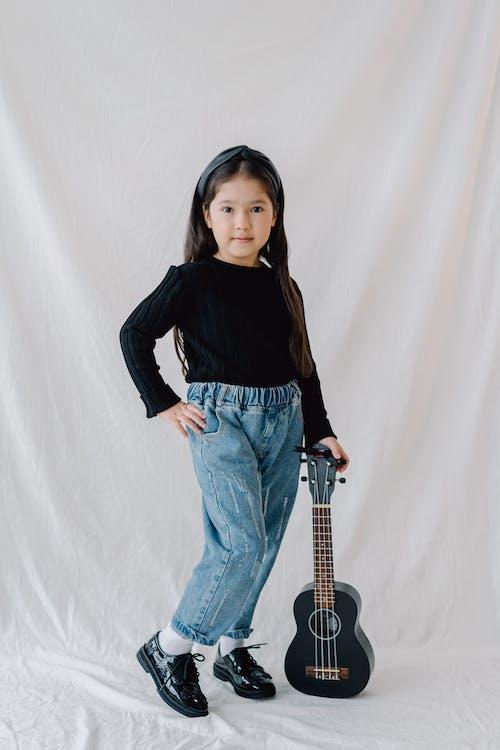 Girl in Black Long Sleeve Shirt and Denim Pants