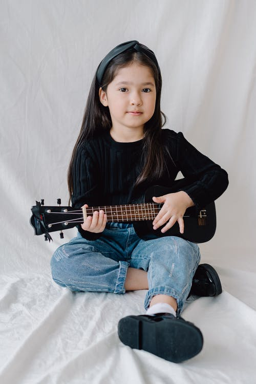 Photo of a Kid Playing the Ukulele while Looking at the Camera