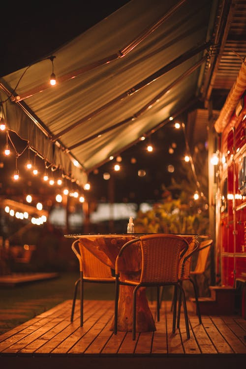 Brown Wooden Table With Chairs and String Lights