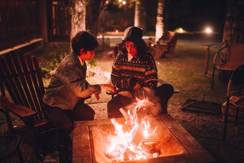 Man and Woman Sitting on Brown Wooden Bench in Front of Bonfire during Nighttime