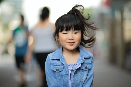 Cheerful Asian preschool girl in denim jacket looking at camera while standing on sidewalk with people in city in windy weather