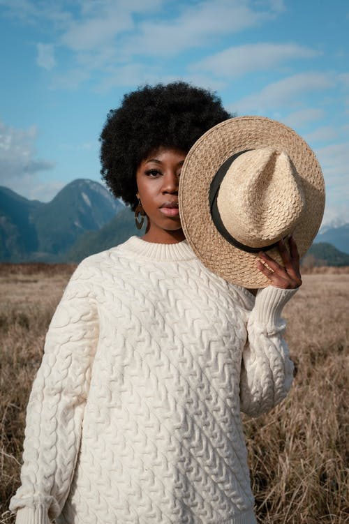 Woman with an Afro Hairstyle Holding a Hat Near Her Face