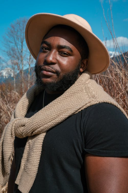 Photo of a Man in a Black Crew Neck Shirt Wearing a Beige Hat