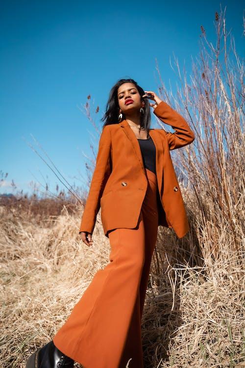 Woman in Orange Coat Standing on Brown Grass Field
