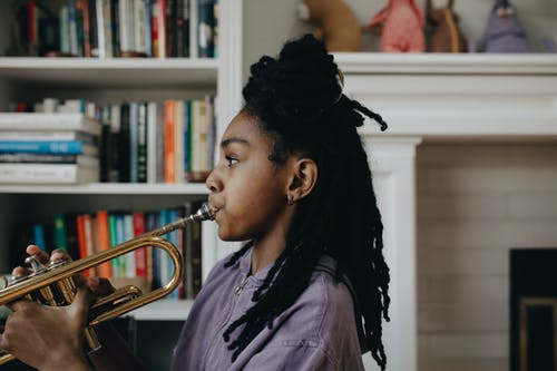 Woman in Purple Shirt Playing the Trumpet