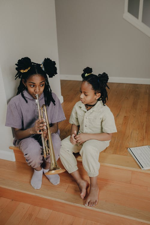 Girl Playing the Trumpet Beside Another Girl