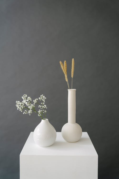 Ceramic vases with wheat ears and blooming branch placed on pedestal in studio against gray background