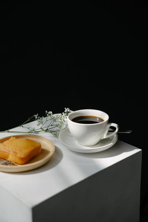 From above of ceramic cup of hot Americano placed near plate with butter cake and blooming branch on pedestal against black background