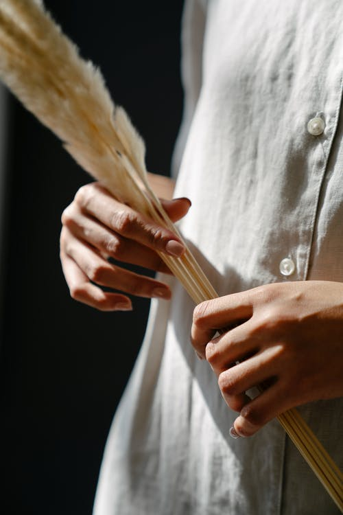 Woman holding long feather in hands
