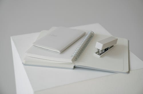 Notepad with stapler and diary with planner on white cube