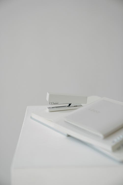 High angle of stapler with blurred stationery placed on white surface against blank wall