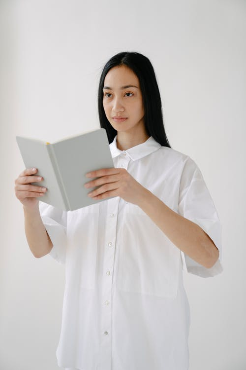 Asian female in white shirt opening notebook and looking away while standing on white background