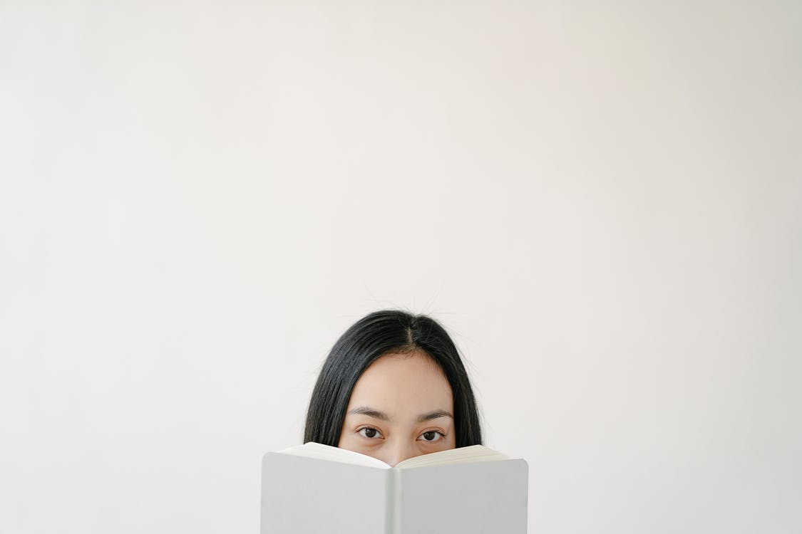 Blank wall with upper part of Asian woman face hidden behind white book