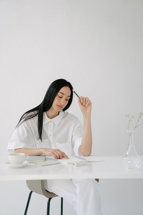 Asian woman scratching head with pencil while reading notepad