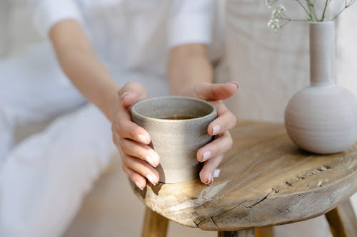 Crop anonymous female with ceramic cup of herbal tea placed on round table near vase of twigs at home
