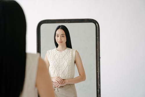 Back view of young Asian female in white and skirt looking at appearance in mirror in studio