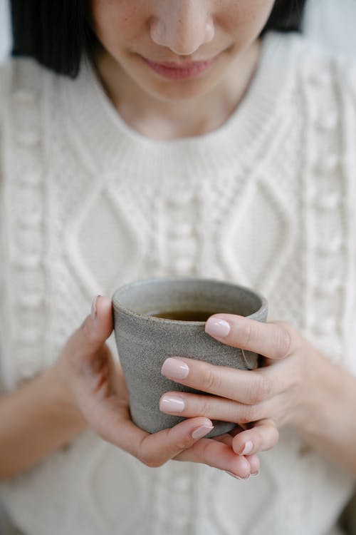 Woman with cup of hot herbal tea