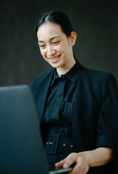 Smiling Asian businesswoman working on laptop