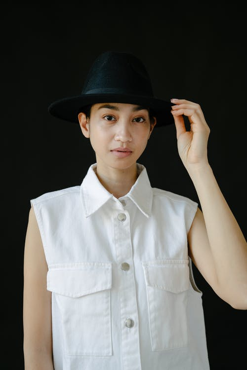 Positive ethnic female with brown eyes touching hat while standing against black background and looking at camera