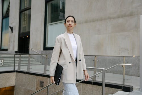 Confident Asian female entrepreneur in stylish outfit and with folder walking in city street and looking away