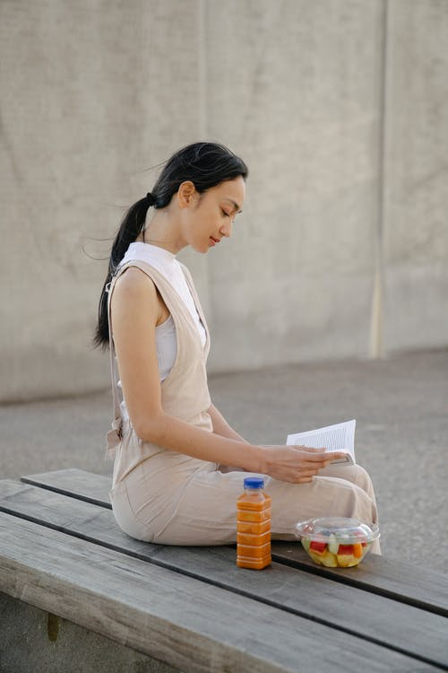 Side view of young ethnic female reading textbook on bench with bottle of drink and fruit salad in town