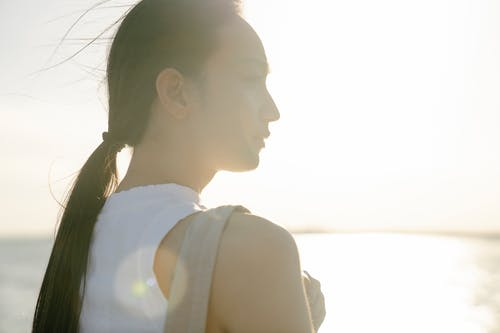 Back view of reflective young Asian female admiring glowing ocean while looking away in sunlight