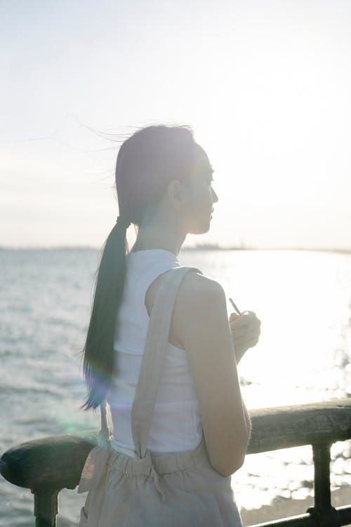 Gentle Asian woman admiring shiny sea from embankment