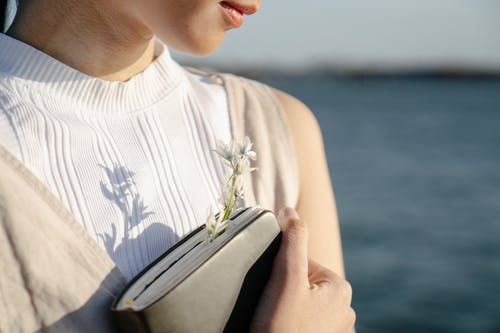 Crop unrecognizable gentle female with blossoming flower in diary against river on sunny day