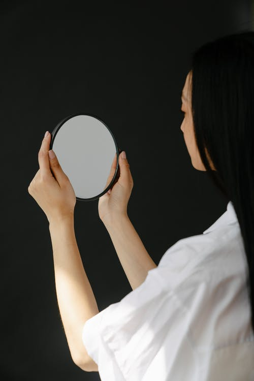 Woman in White Shirt Holding Round Mirror