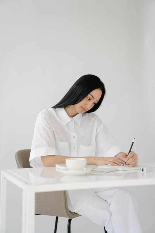 Young Asian lady taking notes in notebook sitting at table in white room