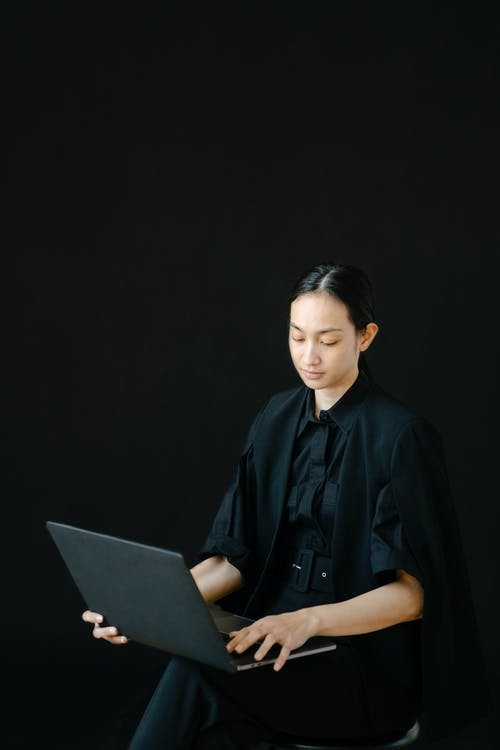 Busy ethnic female entrepreneur typing laptop while sitting on chair
