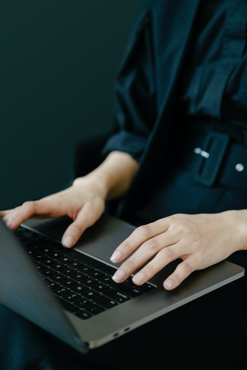 Crop unrecognizable female freelancer in black clothes typing on netbook keyboard while working on project