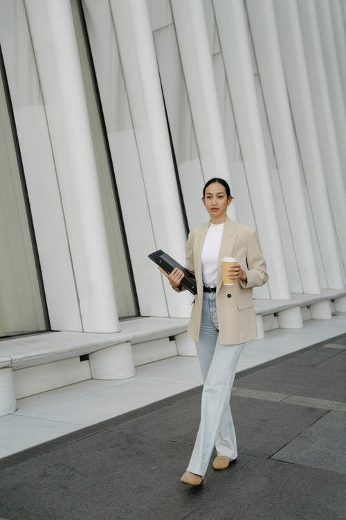 Woman in Beige Blazer and White Pants Standing Near White Wall